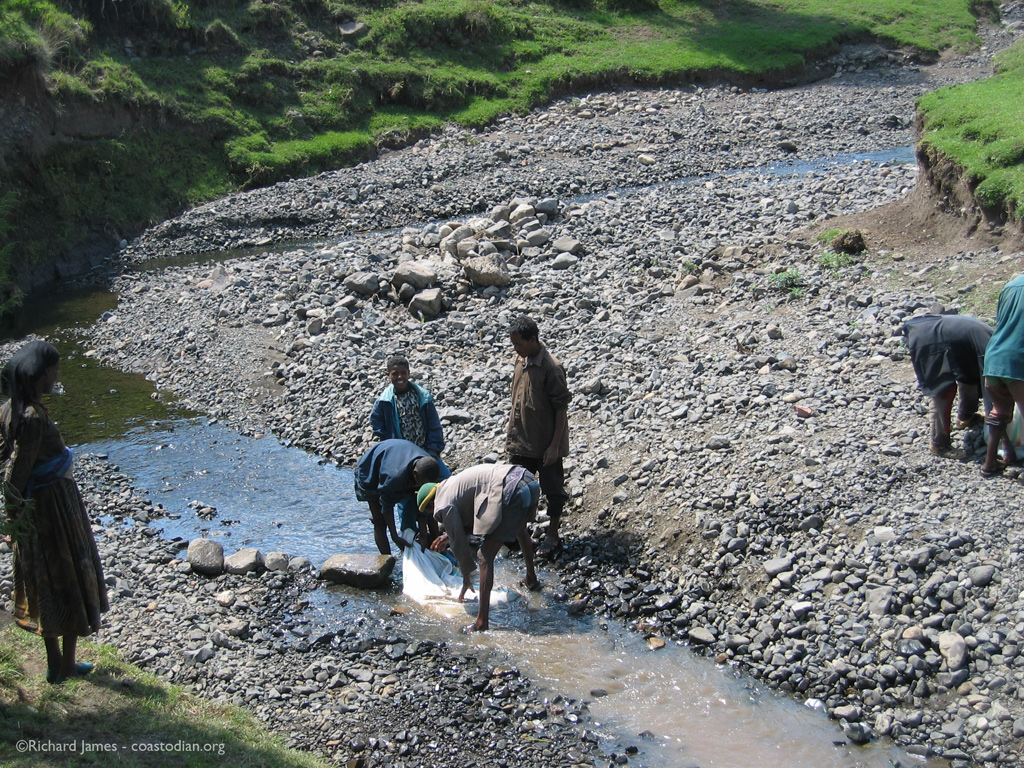 Ethiopians washing a bag of sand in the river. When heavy rains come, this trickle turns to a torrent. Many lives are lost attempting to cross to get to school, market, clinic. Marye, Ethiopia.
