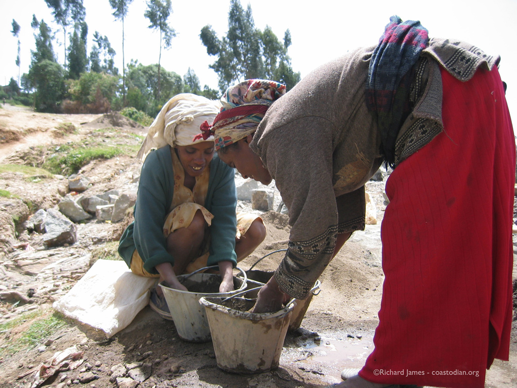 Two women washing river sand in buckets. We mixed concrete on site with hand cracked gravel, locally hewn rocks, river water and cement that was trucked in and hand-carried to the work site. Keranyo, Addis Ababa