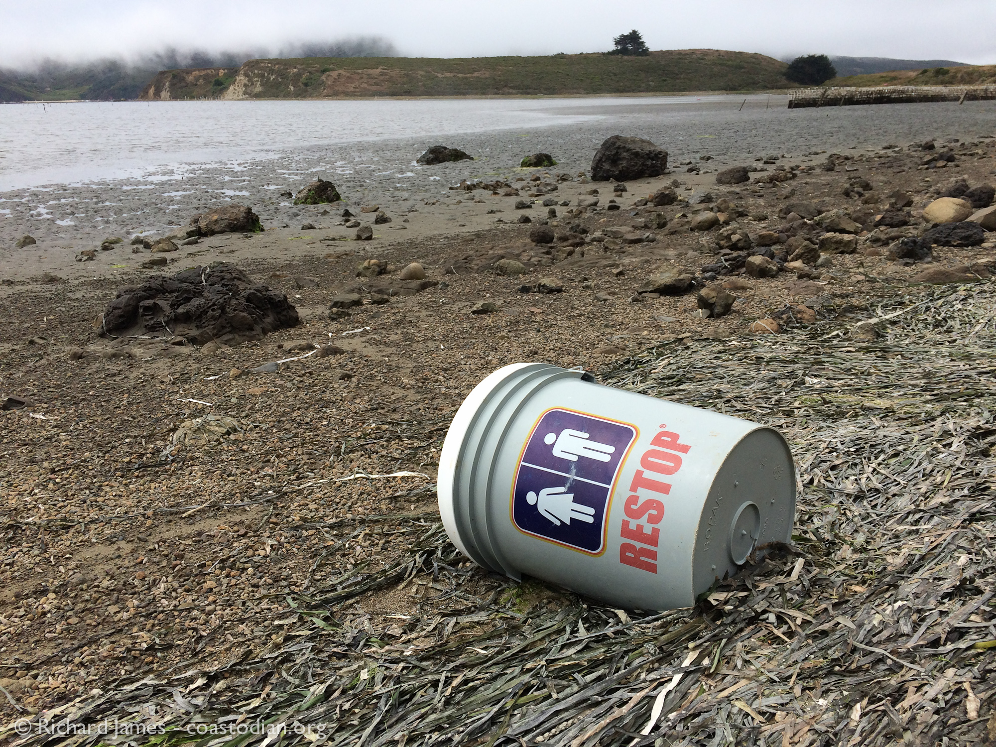 This 5-galloon bucket with seat and sack full of poo inside was found on the northeast shore of Tomales Bay, not far from oyster beds on August, 2016